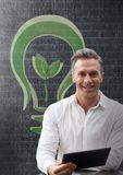 Happy business man at a desk using a tablet against black wall with green graphic Stock Photos