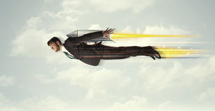 Happy business man flying fast on the sky between clouds royalty free stock image