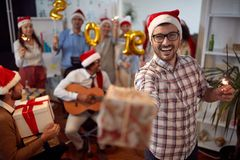 Happy business man have fun in Santa hat and exchange gifts at Xmas party with his colleagues royalty free stock photography
