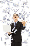 Happy business man holding a laptop and  catching money Royalty Free Stock Photos