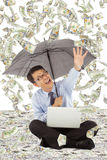 Happy business man holding a umbrella and catching money Stock Photos