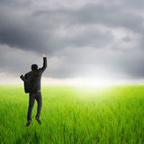 Happy business man jumping in green rice field and rainclouds Royalty Free Stock Photos