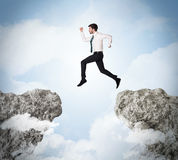 Happy business man jumping over a cliff Royalty Free Stock Images