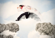 Happy business man jumping over a cliff Royalty Free Stock Photography