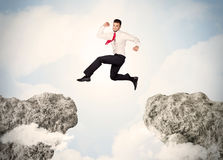 Happy business man jumping over a cliff Royalty Free Stock Image