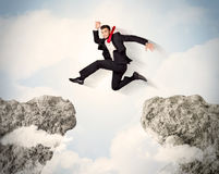 Happy business man jumping over a cliff Royalty Free Stock Photo