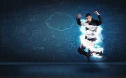 Happy business man jumping with storm cloud around him Stock Photography