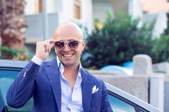 Happy business man looking at you holding adjusting sunglasses outside royalty free stock photography