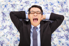 Happy business man lying on the stacks of new taiwan dollar. Background royalty free stock images