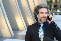 Happy business man making a call with his smartphone outside Royalty Free Stock Photo