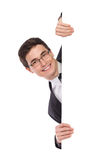 Happy business man peeking behind a banner. Handsome young man peeking behind a banner. Head and shoulders studio shot isolated on white Stock Image