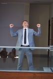 Happy business man raise hands from joy Stock Photos