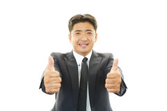 Happy business man showing thumbs up sign Royalty Free Stock Images