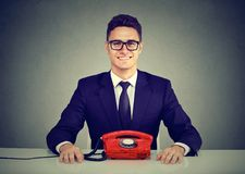 Happy Business Man Sitting At Desk With Vintage Telephone Looking At Camera Stock Photos