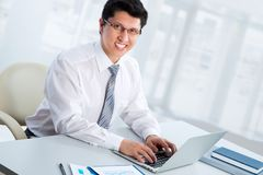 Business man sitting in front of laptop. Happy business man sitting in front of laptop Royalty Free Stock Images