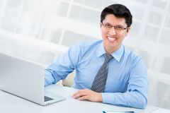 Business man sitting in front of laptop. Happy business man sitting in front of laptop Royalty Free Stock Image