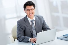 Business man sitting in front of laptop. Happy business man sitting in front of laptop Royalty Free Stock Photo