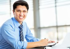 Happy business man sitting in front of laptop. In an office Royalty Free Stock Image