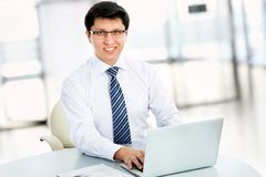 Happy business man sitting in front of laptop Stock Photos
