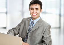 Happy business man sitting in front of laptop Royalty Free Stock Photos