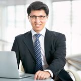 Happy business man sitting in front of laptop. In an office Royalty Free Stock Photo