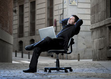 Happy Business Man sitting on Office Chair on Street with Computer Stock Photography