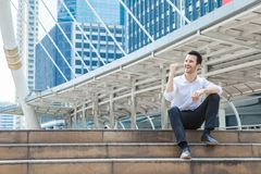 Happy business man smiling and commitment to success sitting on. Stair in downtown Royalty Free Stock Photos