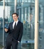 Happy business man smiling outdoors with cellphone Stock Images