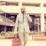 Happy business man talking on his phone while walking outside Stock Photography