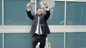 Happy business man throwing dollars in the street.  stock footage