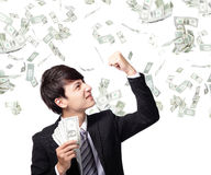 Happy business man with us money. Excited business man earned dollar bills us money under a money rain - isolated over a white background, asian model Stock Image