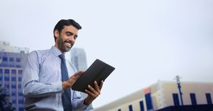 Happy business man using a tablet against city background