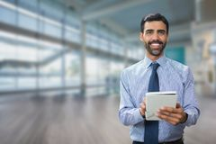 Happy business man using a tablet against office background stock photo