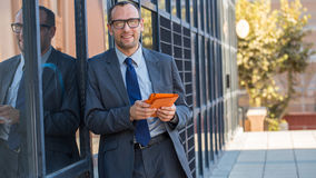 Happy business man using tablet PC in orange cover on a city str Stock Photography