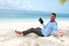 Happy business man working on the beach with pc. Happy business man sitting and working on the beach with tablet computer royalty free stock images