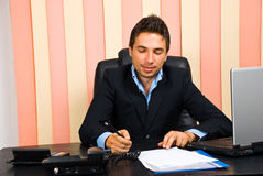 Happy business man write on paper in office royalty free stock image