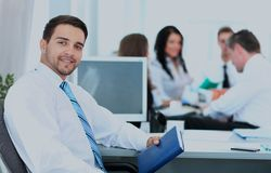 Happy business man with colleagues at a conference in the background. Royalty Free Stock Image