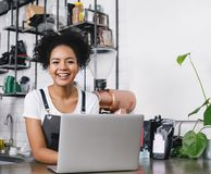 Happy business owner standing at counter. With her laptop royalty free stock image