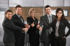 Happy business partners. With thumbs up on office corridor, looking at camera, smiling Royalty Free Stock Images