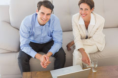 Happy business partners looking at camera sitting on sofa Royalty Free Stock Photos