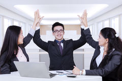Happy business partners raising hands up Stock Image