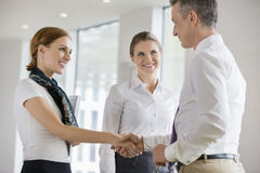 Happy business partners shaking hands in office Royalty Free Stock Images