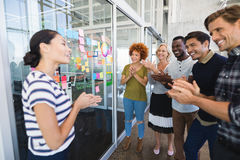 Happy business people applauding. While standing against plan on glass wall in office Stock Photo