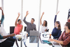 Happy business people with arms raised. Sitting at desk in office Stock Photography