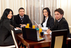 Happy business people around a table at meeting. Four business people in black suits having a business meeting in a modern workplace and sitting on chairs at Royalty Free Stock Images