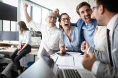 Happy business people celebrating success at company. royalty free stock photo