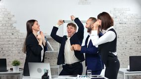 Happy business people celebrating successful deal dancing clapping hand having fun at modern office