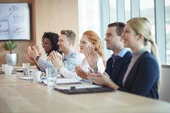 Happy business people clapping at conference table during meeting Royalty Free Stock Images