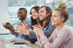 Happy business people clapping at desk Stock Photography
