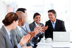Happy business people clapping in a meeting Stock Image